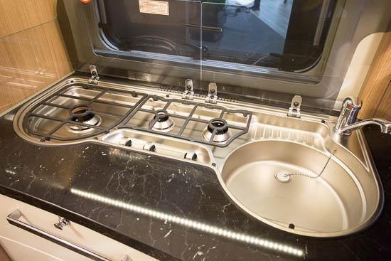 Køkkenet med integreret komfur med smedejernsrist over de tre gasblus