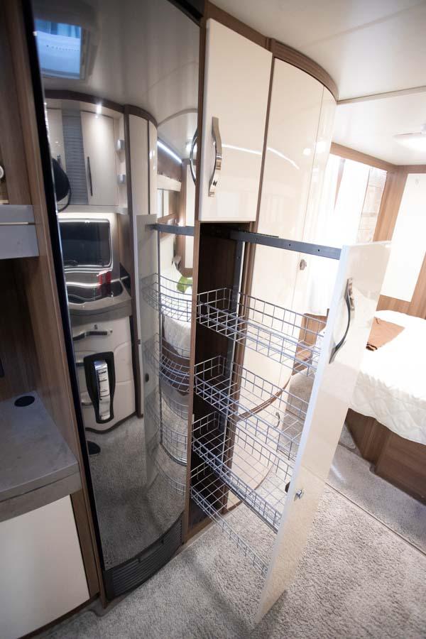 Modsat køkkenet er der er Slimtower-køleskab og et stort udtræksskab med trådhylder.