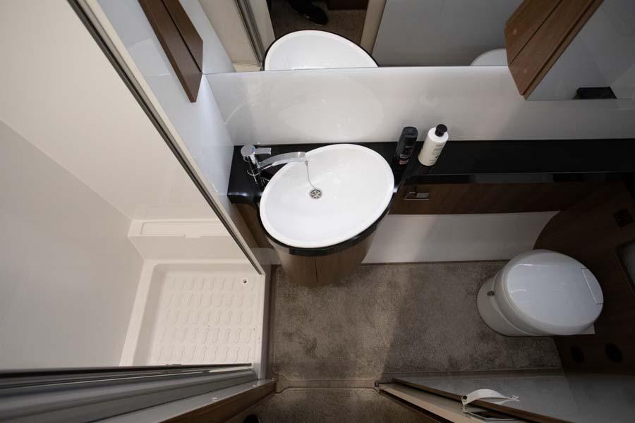 Bagerst i campingvognen er der et stort tværstillet badeværelse med håndvask, skabe, toilet og brusekabine. Det er ikke prangende, men funktionelt, og der er alt hvad man har brug for.