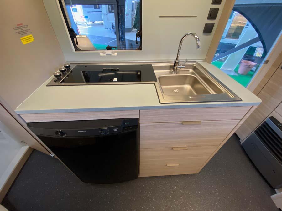 Lille, men velfungerende køkken med køleskab, komfur og vask