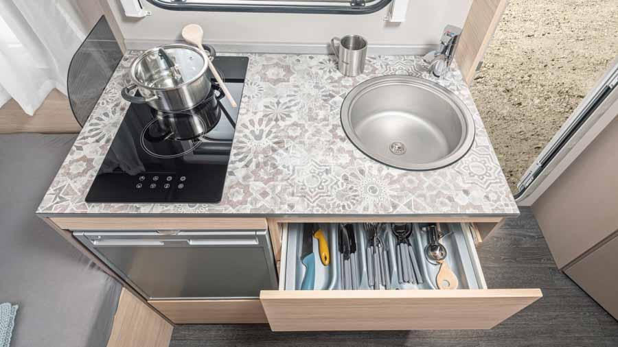 Køkkenet i CaraCito 390Q. Bemærk kompressor køleskabet og det glaskeramiske komfur